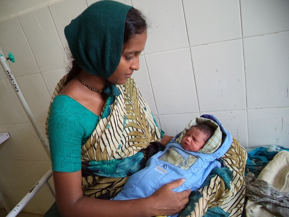 A new mother in Karnataka, India holds her baby in an Embrace warmer.